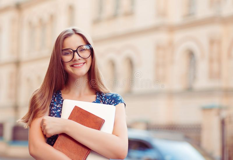 Student young girl woman holding books laptop smiling outside stock photo