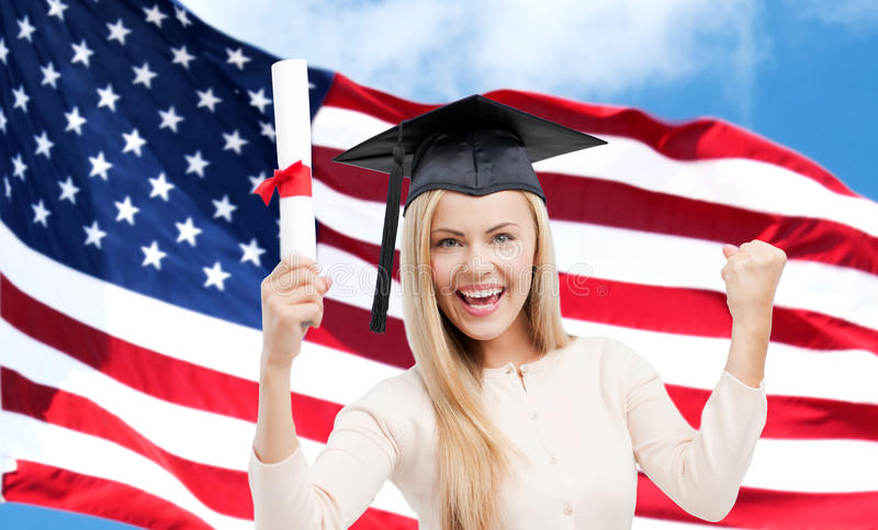 Happy student girl with diploma over american flag. Education, high school, knowledge, graduation and people concept - happy student girl or woman in trencher stock photo