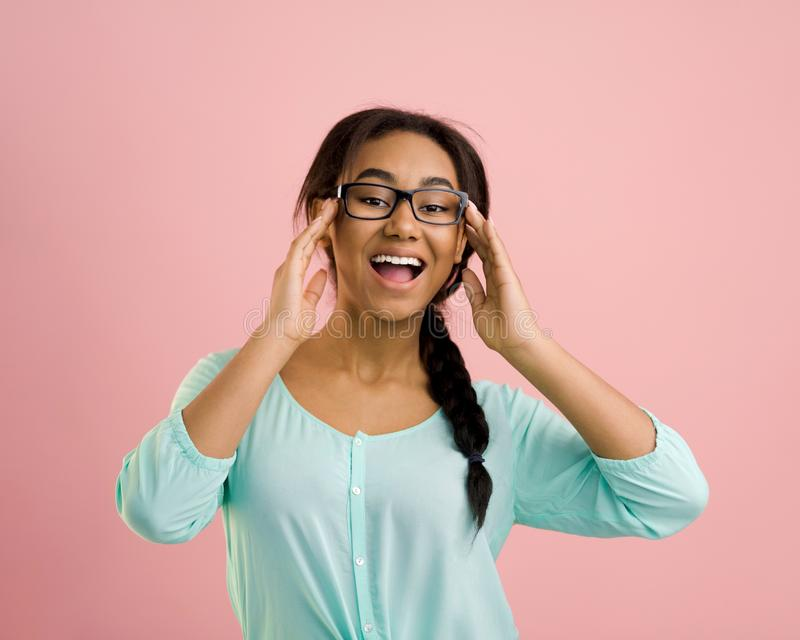 Happy student girl in glasses posing, pink background royalty free stock image