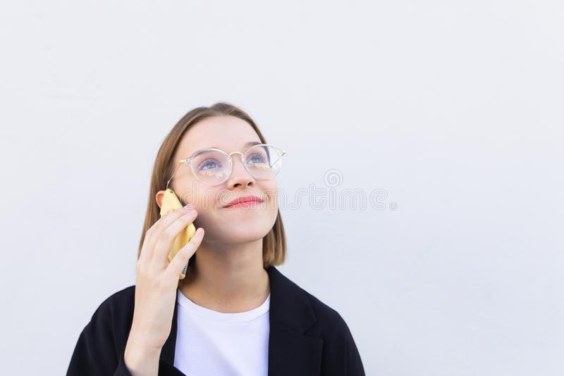 Happy student girl in glasses stands on a white background and talks over the phone royalty free stock photography