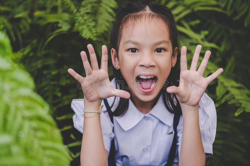 Happy student girl making a scared face in a green garden, for children hapiness and fun concept royalty free stock photography