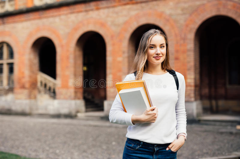 Happy student girl with school bag and notebooks outdoors royalty free stock photography