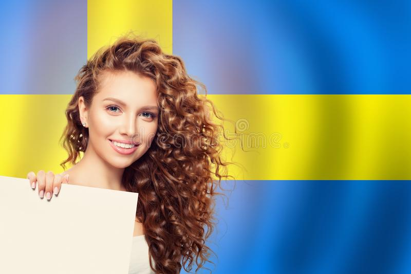 Happy student girl with white empty paper on sweden flag background. Travel and learn Sweden language royalty free stock photography