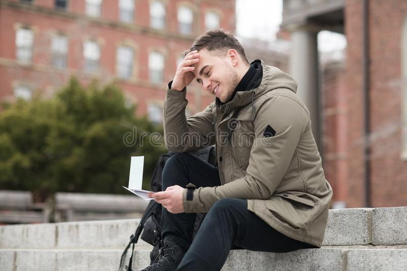 Happy student man reads approval letter after college exams or job offer sitting in campus. Happy student man reads approval letter after college exams or job stock photos