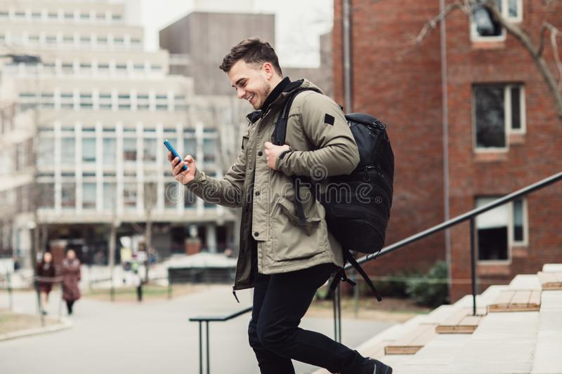 Happy student man text on cell phone walking in city college campus with backpack. stock photos