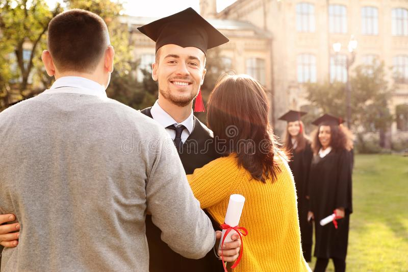 Happy student with parents after graduation ceremony royalty free stock photography