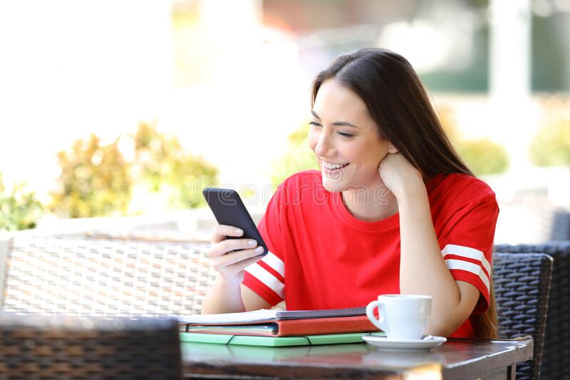 Happy student reading phone content in a coffee shop stock photo
