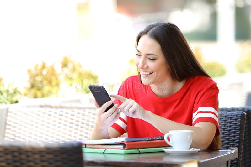 Happy student in red browsing phone content in a bar stock image