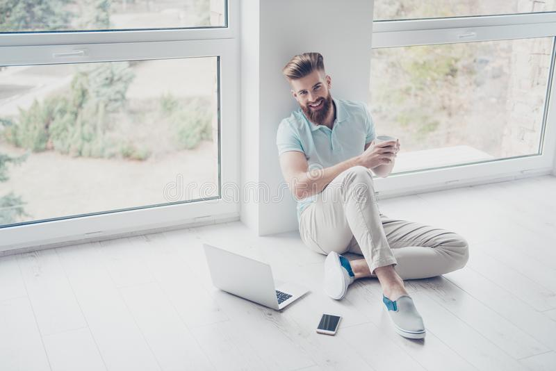 Happy student is sitting on the floor at home relaxing with cup stock photography