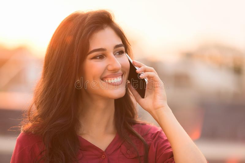 Happy student talking on smartphone, walking at sunset royalty free stock photos