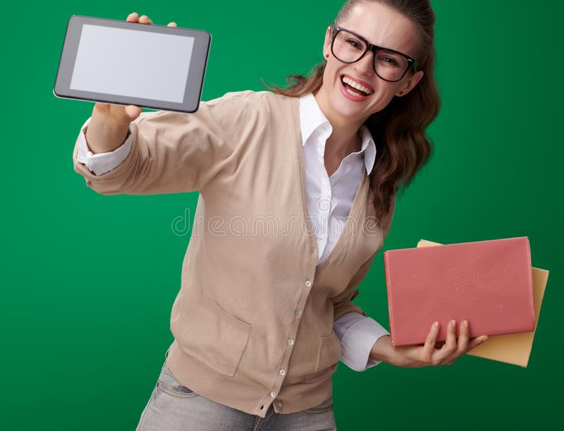 Happy student woman with books showing tablet PC blank screen royalty free stock photo