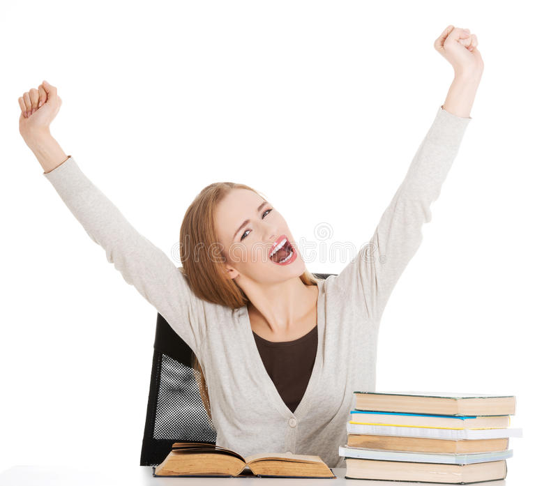 Happy student woman with her hands up and stack of books.