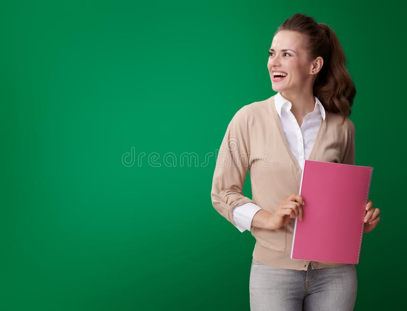 Happy student woman with pink notebook looking at copy space stock photos