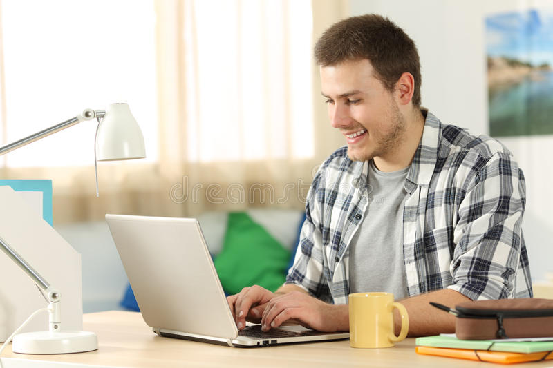 Happy student writing in a laptop in his room stock photography