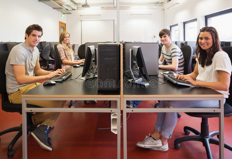 Happy students in computer room. In college stock photo