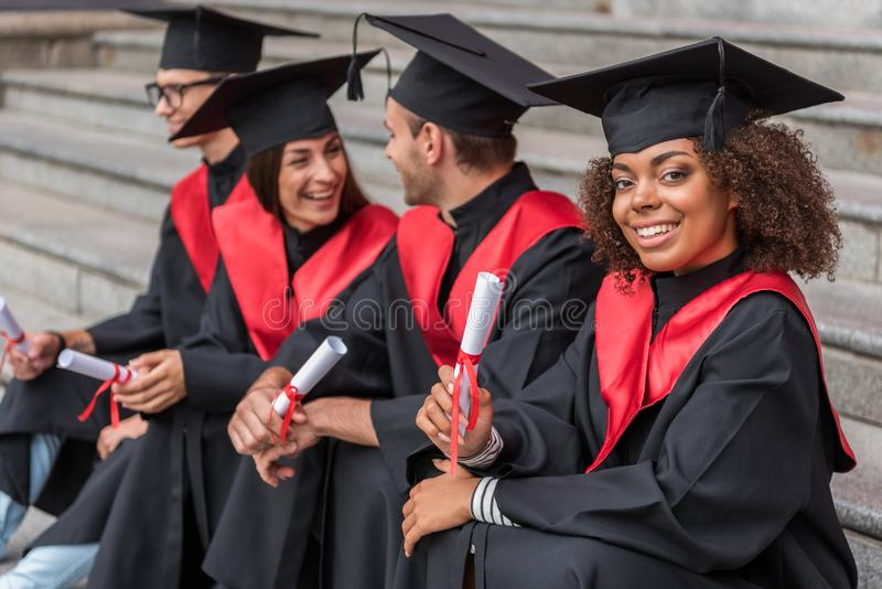 Happy students in graduation gowns and caps. Portrait of excited african girl showing her diploma paper with proud and smiling. She is sitting on stairs near her royalty free stock images