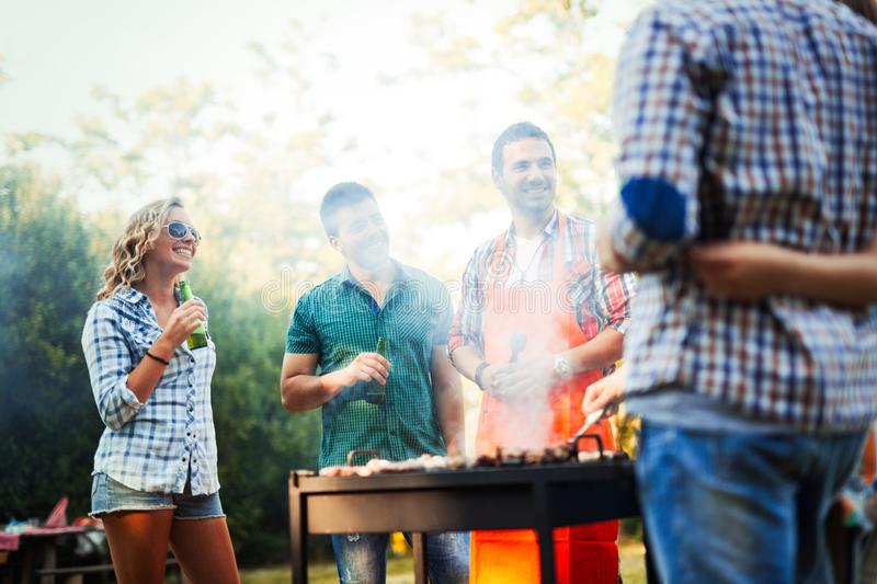 Happy students having barbecue on summer day. In forest royalty free stock photography