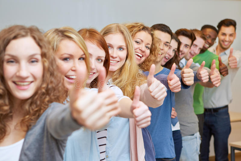 Happy students holding thumbs up stock photos