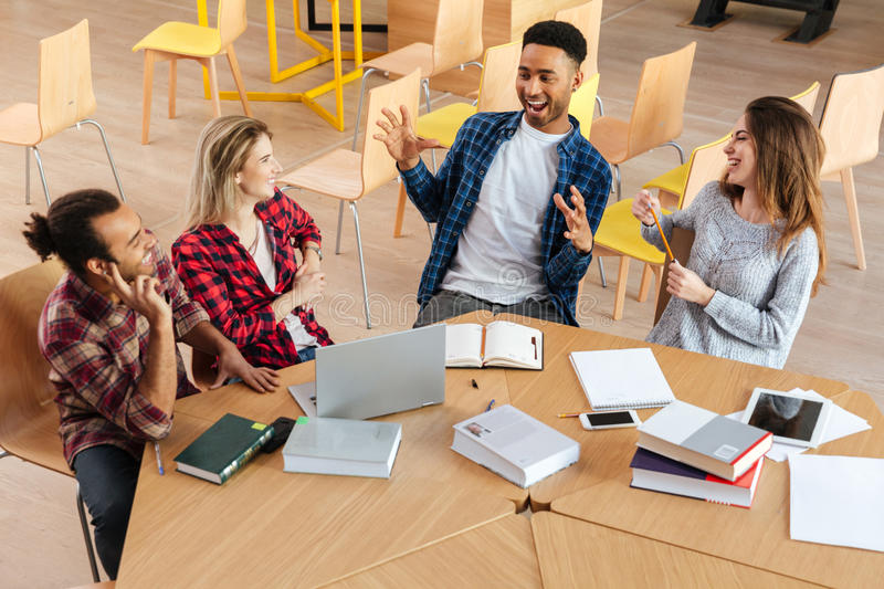 Happy students sitting in library talking with each other. stock images