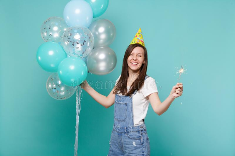 Happy stunning young woman in birthday hat holding burning sparkler and celebrating with colorful air balloons isolated. On blue turquoise background. Birthday stock image