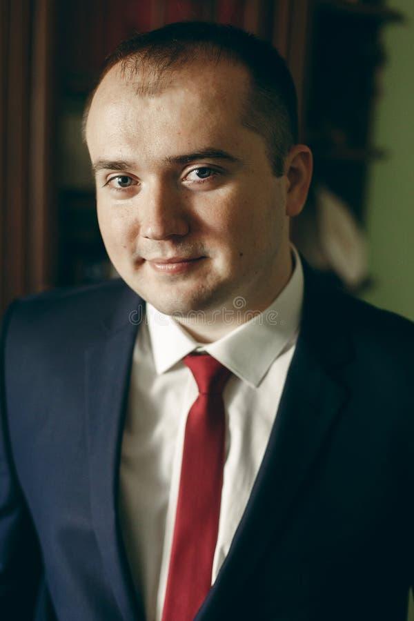 Happy stylish Bräutigam in dunkelblauem Anzug mit roter Krawatte im Hotelzimmer Morgens vor der Hochzeit, Porträt eines glücklich stockfotografie