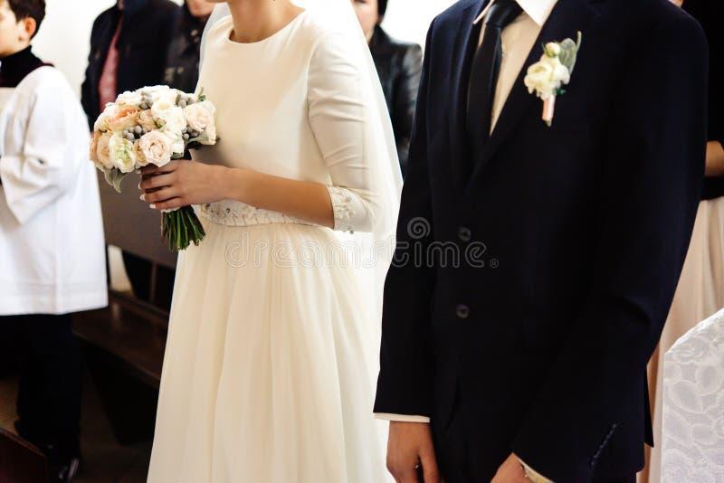 Happy stylish bride and elegant groom sitting at catholic wedding ceremony at church royalty free stock photography