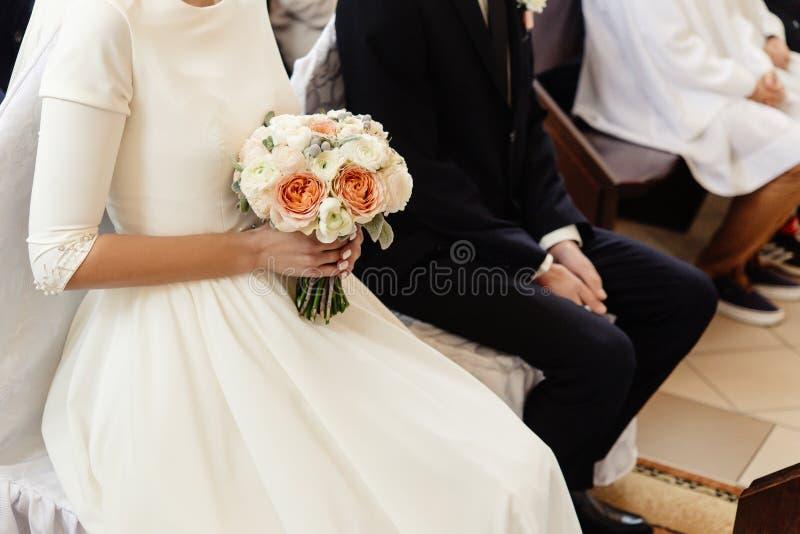 Happy stylish bride and elegant groom sitting at catholic wedding ceremony at church stock images
