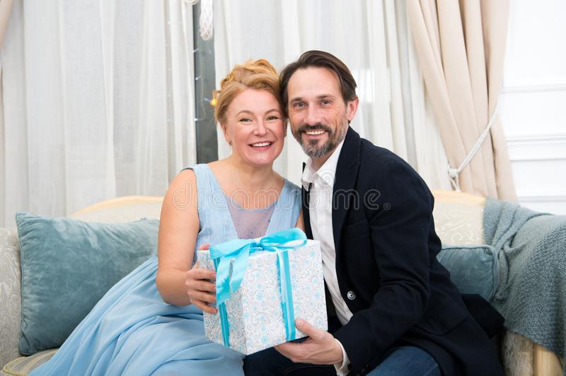 Happy stylish family holding lovely gift box while sitting on cozy sofa royalty free stock images