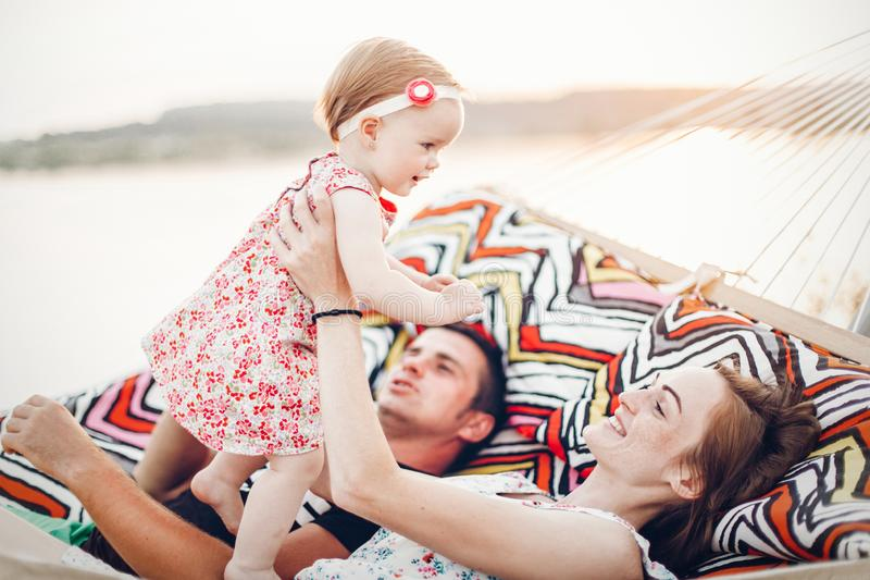 Happy stylish family relaxing in hammock on summer vacation in evening sun light on the beach. hipster couple with child resting stock photo