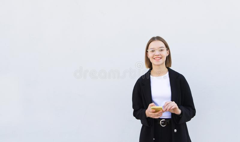 Happy, stylish girl in a jacket and glasses with a smartphone in her hands on a white background stock images