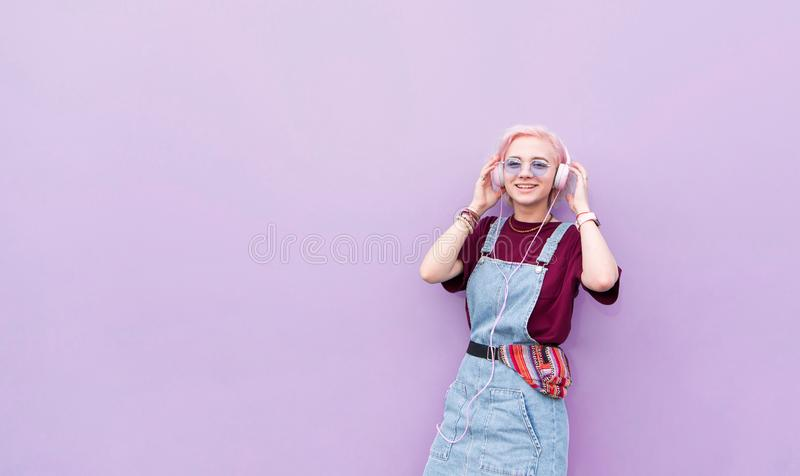Happy, stylish girl with pink hair listening to music in headphones and smiling on a purple background royalty free stock image