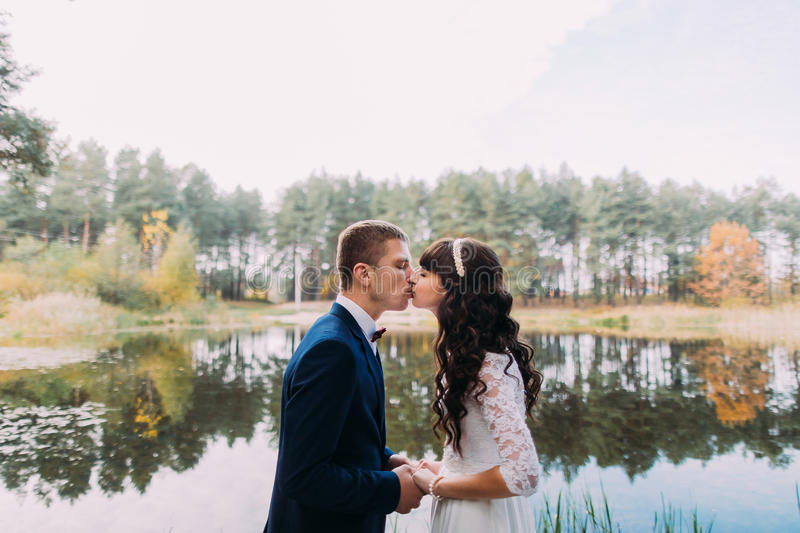 Happy stylish groom and his charming new wife have kiss on the shore of forest lake royalty free stock images