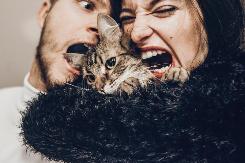 Happy stylish hipster family hugging with their cat. man and woman holding kitty and having fun and taking selfie, happy family m. Happy stylish hipster family royalty free stock image