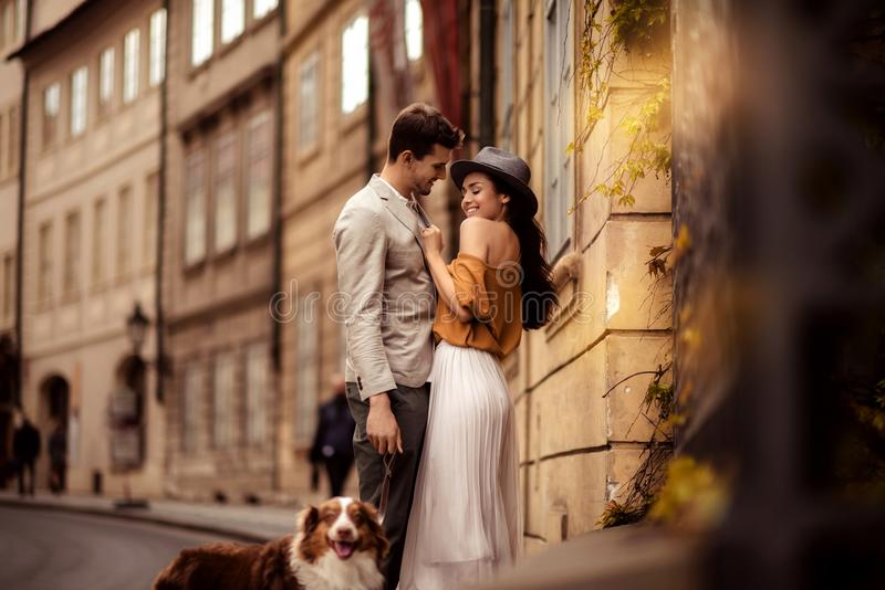 Happy stylish man strolls with dog, embraces his beautiful elegant girlfriend, have good relationship and feel true love royalty free stock photo