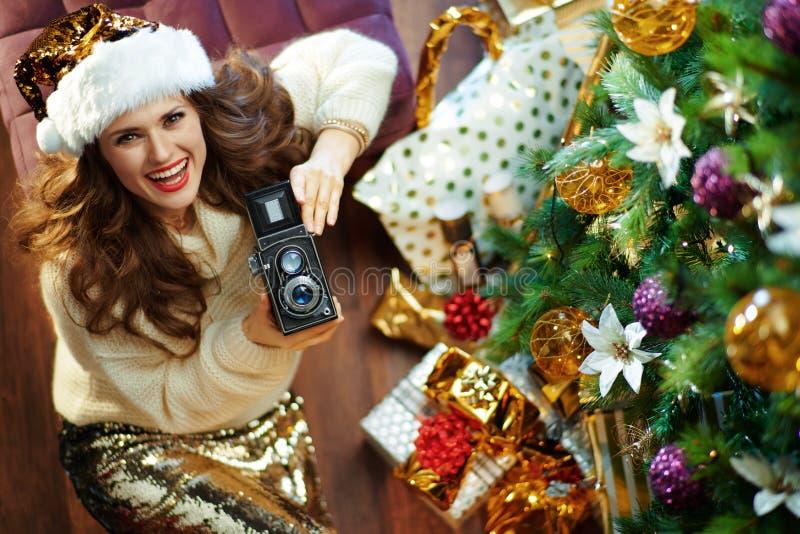Happy stylish middle age woman holding retro photo camera stock photo