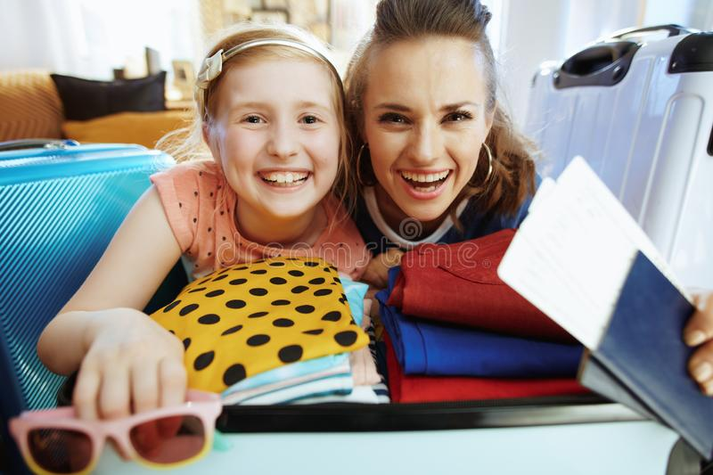 Happy stylish mother and daughter with beach holiday luggage stock images