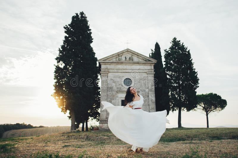 Happy stylish smiling couple walking and kissing in Tuscany, Ita royalty free stock photo