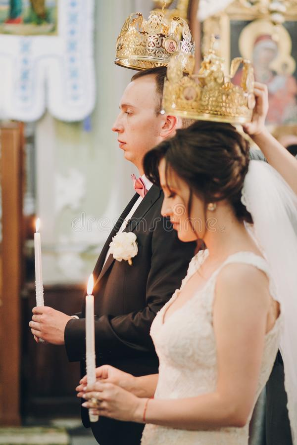Happy stylish wedding couple holding candles with light under golden crowns during holy matrimony in church. Bride and groom. Standing at wedding ceremony royalty free stock photography