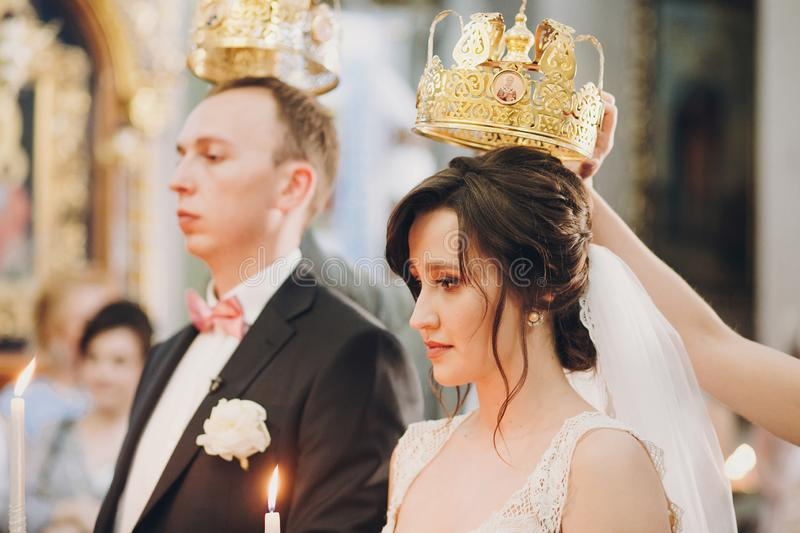 Happy stylish wedding couple holding candles with light under golden crowns during holy matrimony in church. Bride and groom. Standing at wedding ceremony stock photo