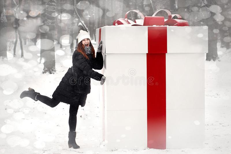 Happy stylish woman holding big present box with red ribbon with stock images