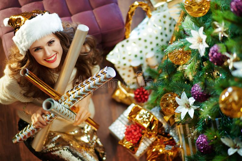 Happy stylish woman holding wrapping paper rolls stock photo