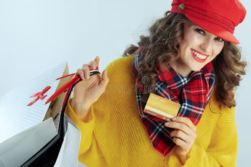 Happy stylish woman shopper showing golden credit card royalty free stock photo
