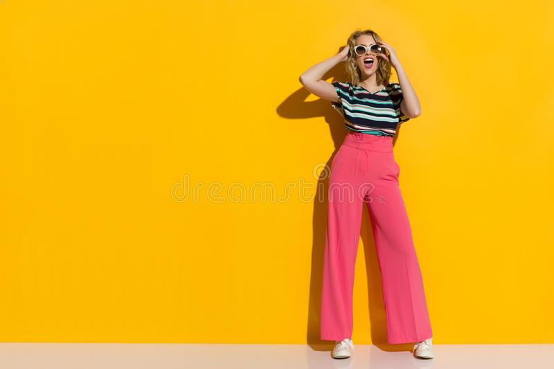 Happy Stylish Woman In Sunglasses, Pink Wide Legs Trousers, Sneakers And Striped Blouse Is Shouting stock photography