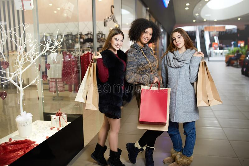 Happy stylish young multiethnic women with shopping bags walking in shopping mall with paper eco bags. Caucasian and royalty free stock image