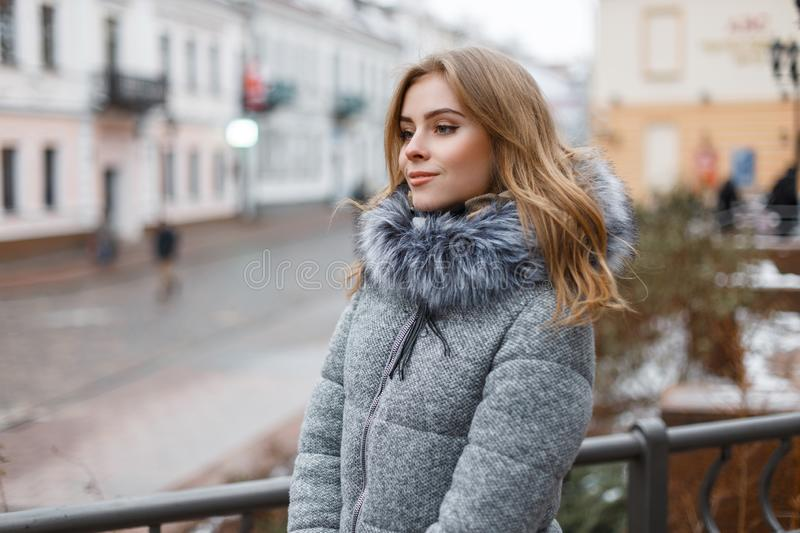 Happy stylish young woman in a gray knitted hat in a fashionable winter coat with fur in knitted warm mittens. With a beautiful smile walks around the city on a royalty free stock photo