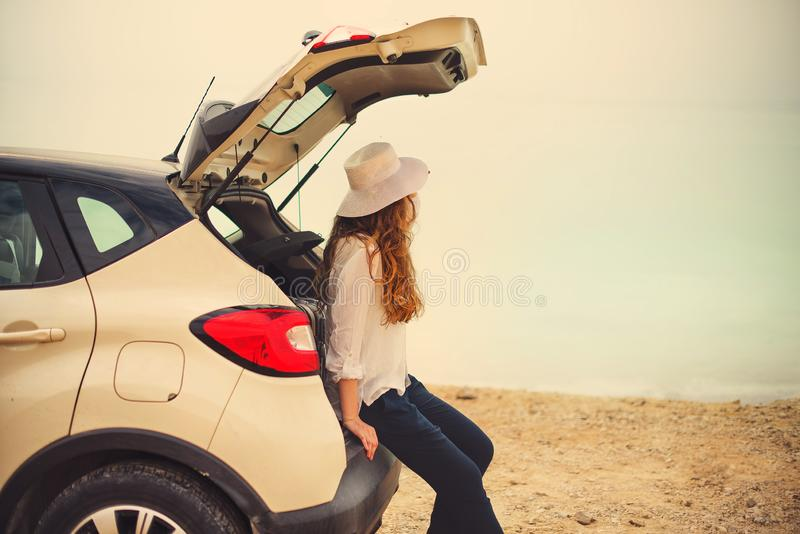 Happy stylish young woman traveler on beach road sitting on white crossover car, holding hat in hand. Banner. Travel, summer. Vacation, holiday, freedom concept royalty free stock images
