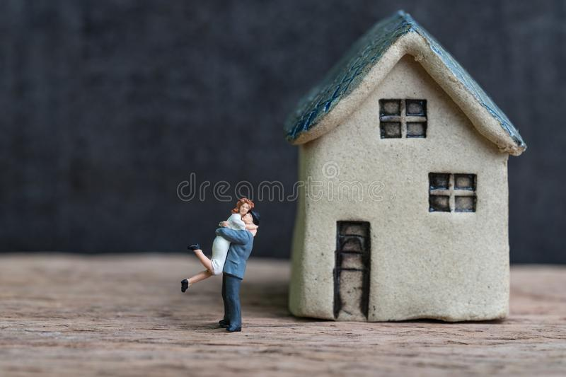 Happy success marriage love life concept, miniature lovely couple husband and wife with small house on wooden table and black royalty free stock photos