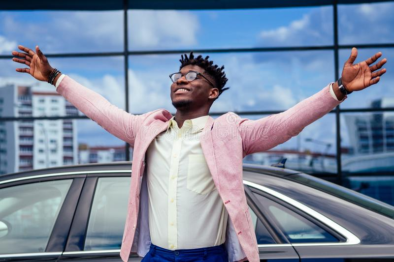 Happy and successful afro american businessman rejoices and enjoying success ahead of the car. concept of a good deal. And victory royalty free stock images