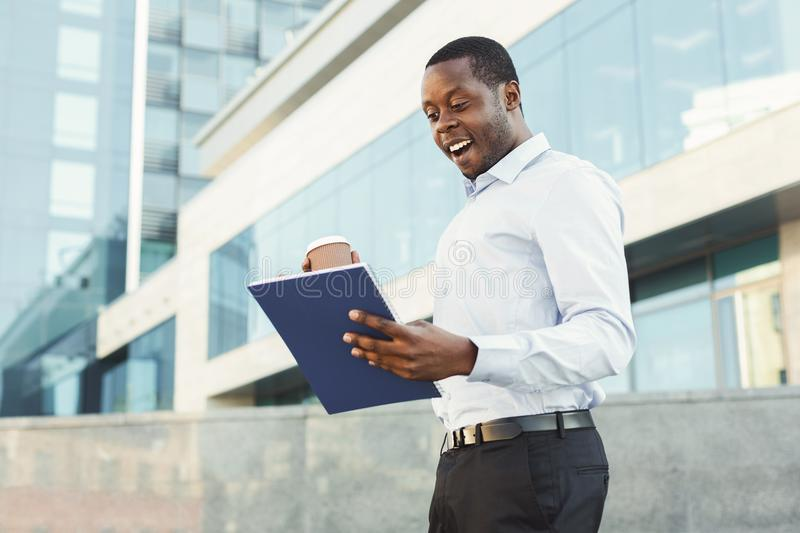Happy successful black businessman seeing great income in the report. stock images