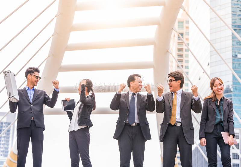 Happy Successful business group People Hands Raised successful with city background Successful business group with arms up stock photos